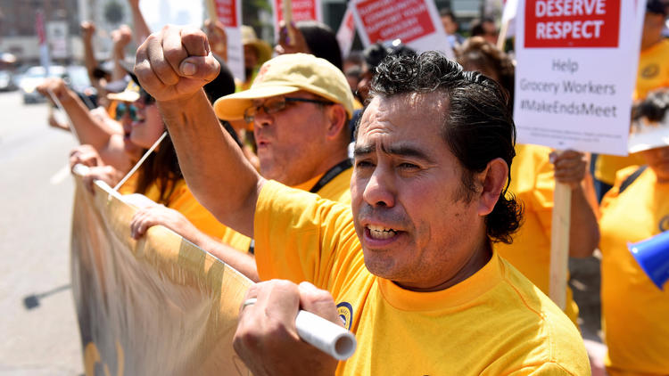 Oscar Gonzalez, a Ralphs produce worker in Hollywood, marches with grocery workers and supporters Tuesday to demand a new contract. (Michael Owen Baker / For The Times)
