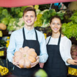 Joyful employees posing with big pumpkin at vegetables market and smiling