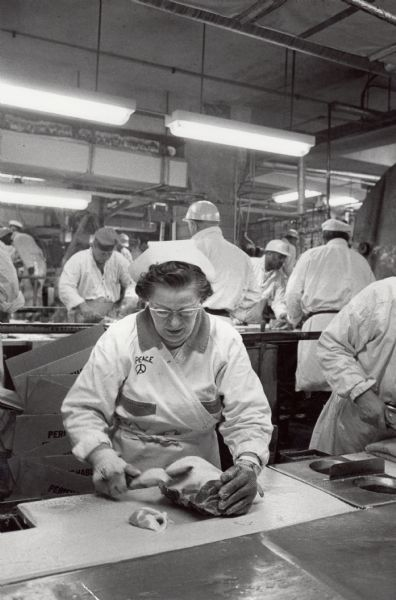 A woman worker on the poultry line at an unidentified packer, probably in Chicago. All of the other workers in the photograph, all of whom were represented by the Amalgamated Meatcutters and Butcher Workmen of North America, are men. The peace symbol of the 1960s has been drawn on the women's uniform.