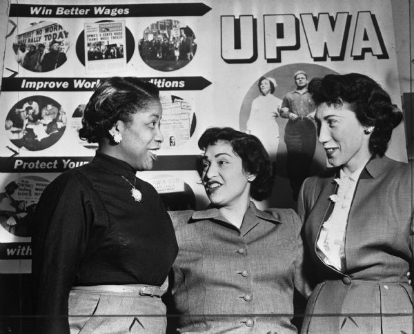 Delegates to the first Women's Activities Conference sponsored by the United Packinghouse Workers of America. A sign behind the three women concerns the importance of labor unions for women.