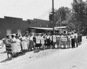 "Women workers on strike against the Holly Farms Poultry Company, posed outside for a ""solidarity"" picture. Dorothy Johnson, wearing the third picket sign from the left, was the head of the strike committee."