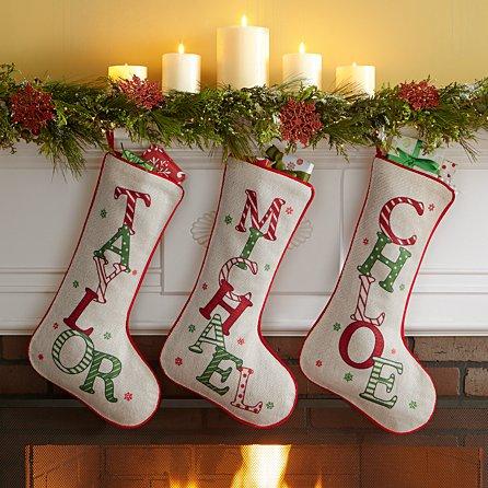 Three Christmas stockings hang on a mantle