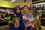 Two UFCW members hold red white and blue themed flowers in the floral section of a grocery store