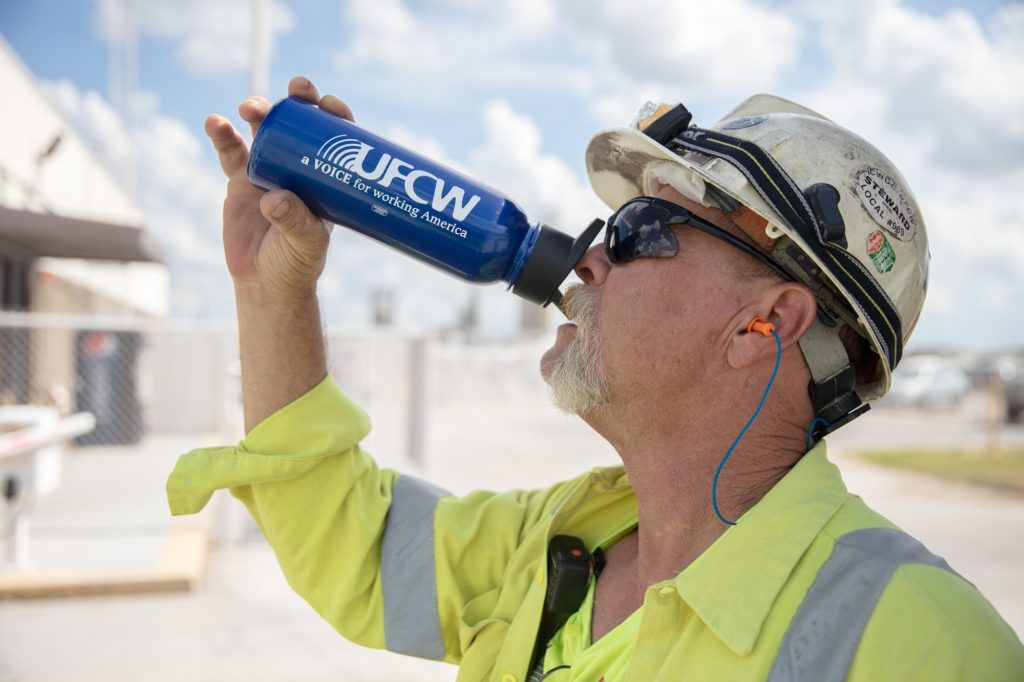 Man in hardhat outside drinks from a UFCW water bottle
