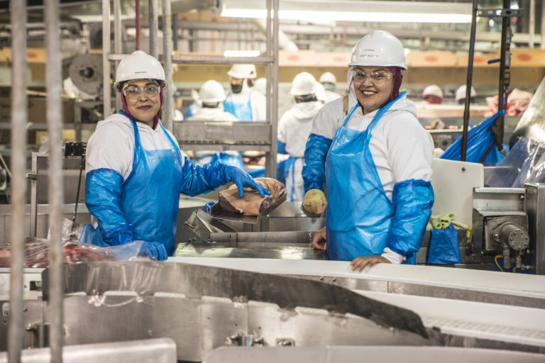 Two women who are UFCW 1149 members in a meatpacking plant