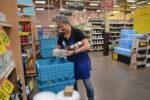 Woman at Kroger stocks shelves from blue bins