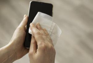 Woman disinfecting phone