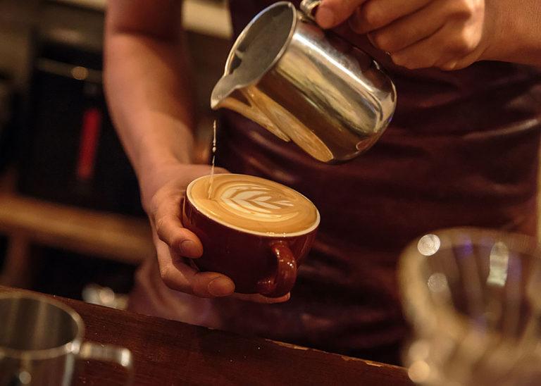 A barista pours hot milk foam to create latte art in a mug