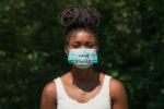 A young Black woman wears a face mask during global pandemic that says