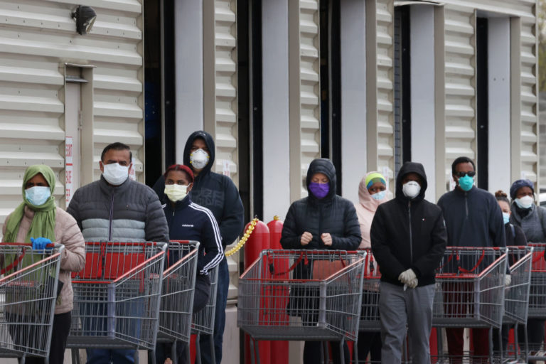 Customers wear face masks to prevent the spread of the novel coronavirus as they line up to enter a store