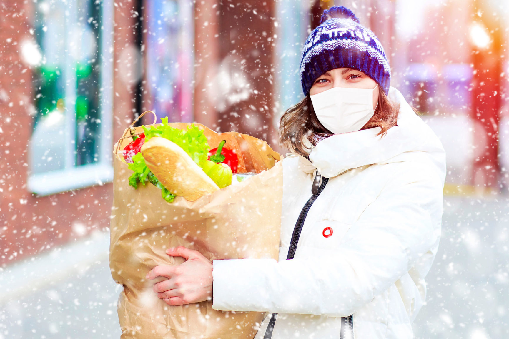 Woman wearing mask grocery shopping during holidays