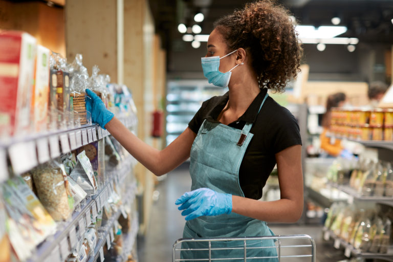 Supermarket and retail. One young supermarket employee sorting products on the shelfs