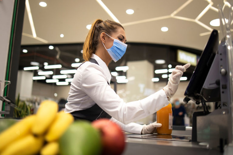 Grocery Cashier Wearing Mask While Working