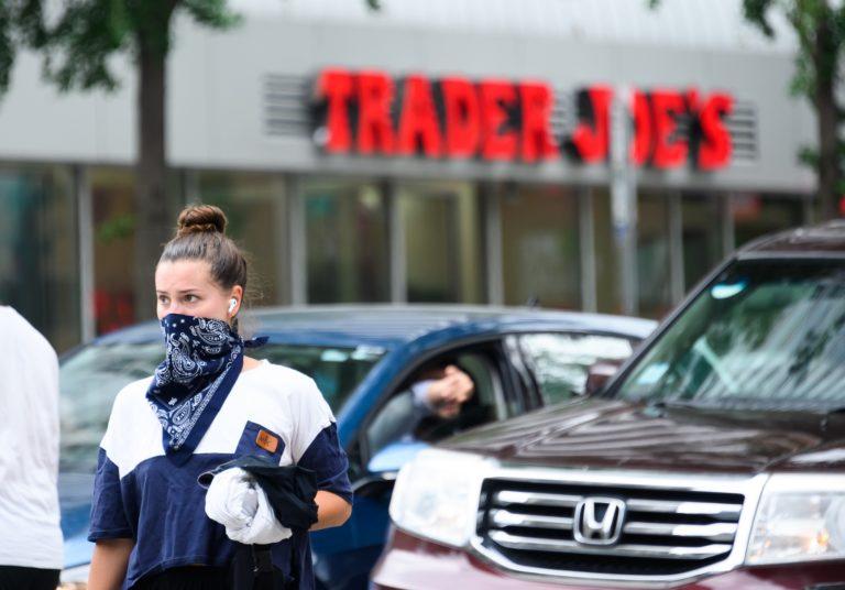 A person wears a bandana face covering outside of Trader Joe's