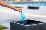 Woman throwing used protective surgical mask into the garbage bin
