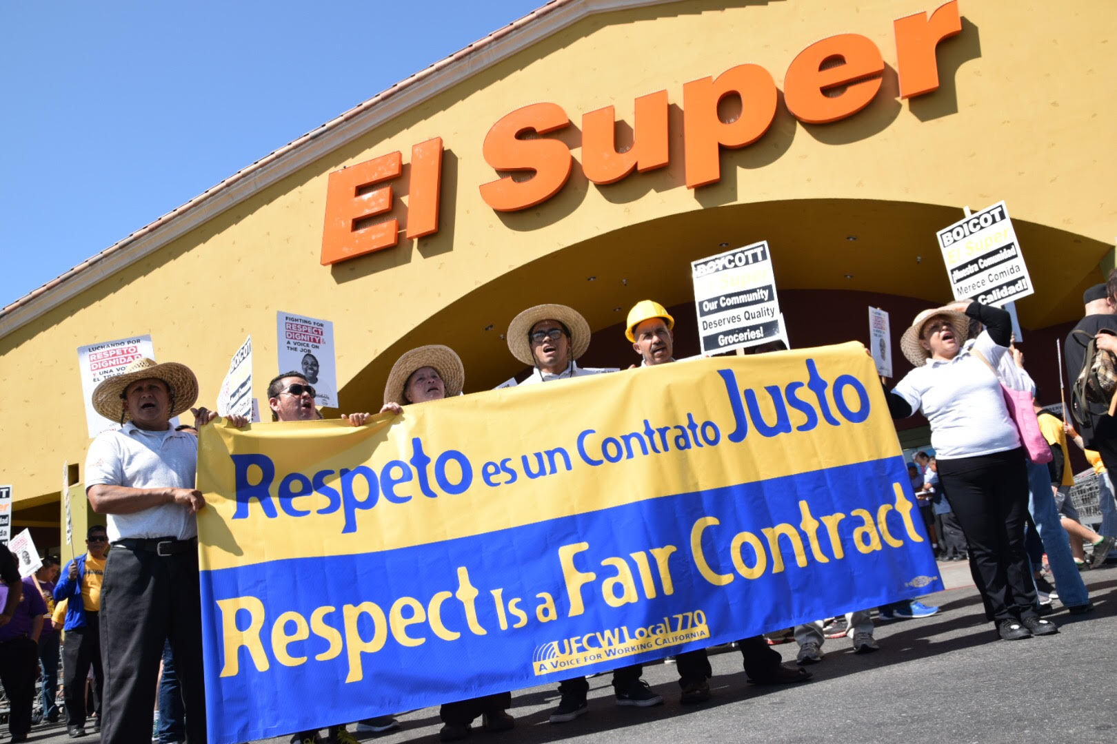 "UFCW members hold a ""Respect is a Fair Contract"" sign outside of El Super"